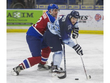 Saskatoon Blades forward Cameron Hausinger moves the puck away from Edmonton Oil Kings defenceman Kyle Yewchuk in second period WHL action, November 28, 2015.