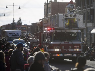 Saskatoon Firefighters mascot Sparky the Fire Dog waves as the Santa Claus parade makes its way down Second Avenue North in Saskatoon, November 15, 2015.