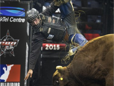 A bull rider flies through the air after a ride at PBR Canadian Finals Bull Riding  in Saskatoon at SaskTel Centre, Friday, Nov. 20, 2015.