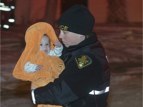 A Saskatoon police officer carries a baby to be checked out my MD Ambulance at the scene of a duplex fire in the 100 block of Imperial Street, Monday, November 30, 2015.