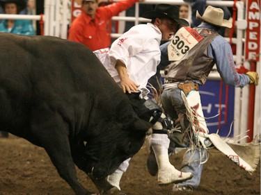 Bullfighter Scott Bryne gets between Jody Turner of Coachran, Alta. and a bull named High Voltage  at the  Canadian Rodeo Tour Championship in Calgary in 2008.