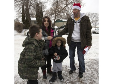 Radio station C95, the Kinsmen Club of Saskatoon and other sponsors surprised Janelle Bruneau and her sons, Tyler and Trey, with a Christmas Wish, December 14, 2015.  They were surprised with toys, groceries, gifts and even a car — courtesy of Precision Auto Body. Here Rob Suski greets the family.