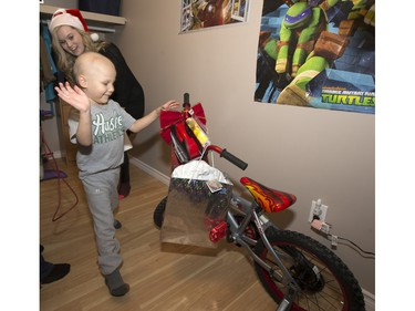 Radio station C95, the Kinsmen Club of Saskatoon and other sponsors surprised Janelle Bruneau and her sons, Tyler and Trey, with a Christmas Wish, December 14, 2015.  They were surprised with toys, groceries, gifts and even a car — courtesy of Precision Auto Body. Here Trey sees his new bike.