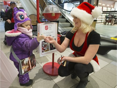 Megan Schindel is a Salvation Army kettle volunteer who dresses up as Santa and sings in the Midtown mall. Here she gives a candy cane to two-year-old Rachel Best after the little girl made a donation, December 16, 2015.