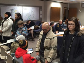 A group of people turned their back on a meeting of the Saskatoon board of police commissioners on Dec. 10, 2015 to show their opposition to the practice of police street checks.