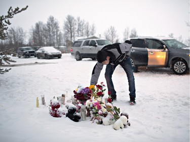 A resident of La Loche pays his respects on January 23, 2016 to the victims of a Friday school shooting. The shooting left four people dead.