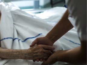 (FILES) A file picture taken on July 22, 2013 shows a nurse holding the hand of an elderly patient at the palliative care unit of the Argenteuil hospital, outside Paris. A panel set up at the request of President Francois Hollande on December 16, 2013 recommended legalising assisted suicide in France, where the debate on euthanasia has re-emerged after several end-of-life tragedies. The suicides of two elderly couples in November and the heartwrenching testimony of a politician who watched her terminally-ill mother die after taking pills have shocked and moved France, where euthanasia is illegal.AFP PHOTO / FRED DUFOURFRED DUFOUR/AFP/Getty Images ORG XMIT: POS1312161151512310 ORG XMIT: POS1504101413518393 // 1211 na euthanasia ORG XMIT: POS1511261852413923