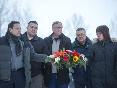Federation of Saskatchewan Indian Nations Chief Perry Bellegarde, left, La Loche acting mayor Kevin Janvier, Premier Brad Wall, Public Safety Minister Ralph Goodale and Local MP Georgina Jolibois lay down flowers at a memorial at La Loche Community School on January 24, 2016.
