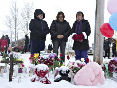 Residents of La Loche say a prayer in front of a makeshift memorial at La Loche Community School on January 24, 2016. A Friday shooting left four people dead.