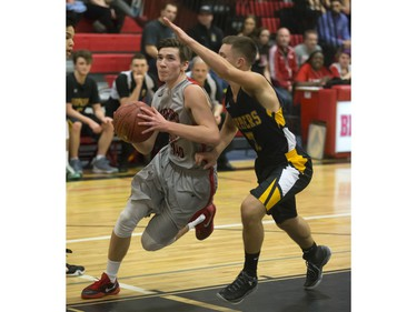 Brett McMurtry of the Bedford Road Collegiate RedHawks (L) drives against Mina Ogot of the Garden City Fighting Gophers during opening game action in the annual BRIT basketball classic, January 7, 2016.