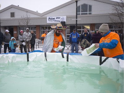 Polar Dippers add ice to a small pool prior to the Polar Dip to fight human trafficking at the Farmers market on Saturday, February 27th, 2016.