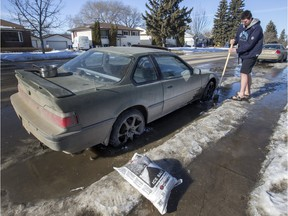 Aiden Rosvold was using pots of hot water, salt and an ice chipper to try and free his vehicle from the ice which had frozen in his rims for the past two days on Broadway Avenue, Friday, February 26, 2016.