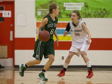 Holy Cross Crusaders Katriana Philipenko moves the ball against St. Joseph Guardians Jordan Zemiak in the City girls high school basketball city final at Bedford Road Collegiate on Saturday, March 12th, 2016.