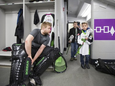 Nine-year-old Cohyn Wells enters the locker room and is greeted by Rush goalie Tyler Carlson, following Wells' signing of a one-day contract with the Saskatchewan Rush, March 26, 2016. Wells is the Saskatchewan representative for the Children's Miracle Network's Champion Program.