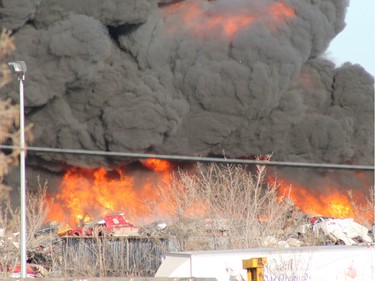 A crowd gathered to watch firefighters battle a blaze at an auto salvage yard at Avenue P and 14th Street West in Saskatoon on April 19, 2016.