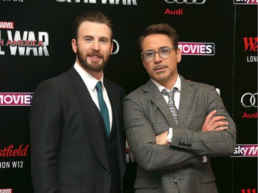 """Actors Chris Evans (L) and Robert Downey Jr. pose for photographers upon arrival at the European premiere of """"Captain America: Civil War"""" in London, England, April 26, 2016."""