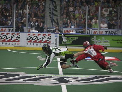 Saskatchewan Rush #74 Jeremy Thompson (L) takes a dive after colliding with Calgary Roughnecks defence #16 Mike Carnegie at SaskTel Centre in Saskatoon, May 21, 2016.