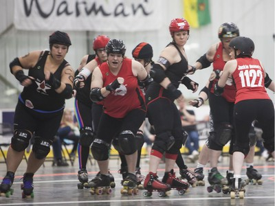 Unicorn Thunder (Centre left) of the Saskatoon Mindfox blocks the other team's jammer during the Attack of the 8 Wheeled Woman Roller Derby Tournament in Warman, May 14, 2016.