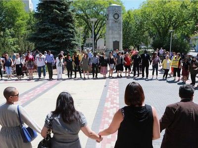 Residents of Saskatoon share a round circle dance during World Refugee Day put on by the Saskatoon Refugee Coalition at Civic Square at City Hall in Saskatoon on June 20, 2016.