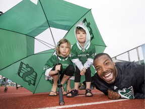 Shamawd Chambers of the Saskatchewan Roughriders mugs for the camera with young fans Emilie and Sophia Hvidston at Rider training camp at Griffiths Stadium in Saskatoon, Friday, June 03, 2016. Sophia is a blood recipient and, with Chambers, helped launch Canadian Blood Services Bleed Green program for season seven.