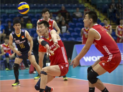 Chen Zhang of China (C), with teammate Jianjun Cui (R), returns service against Portugal during FIVB World Volleyball League action at Sasktel Centre in Saskatoon, June 24, 2016.