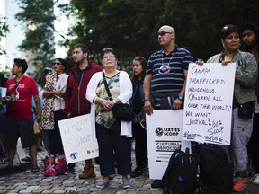Dokis Thibault, centre, gathers with supporters for a demonstration at a Toronto courthouse on Tuesday, August 23, 2016. Scores of aboriginals from across Ontario rallied in Toronto today ahead of a landmark court hearing on the so-called '60s Scoop.