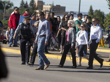 """RCMP members escort a family across the street from North Battleford Provincial Court to the detachment through hundreds of protesters chanting """"Justice For Colten,"""" Colten Boushie, the 22-year-old that was fatally shot last week allegedly by Gerald Stanley, August 18, 2016."""
