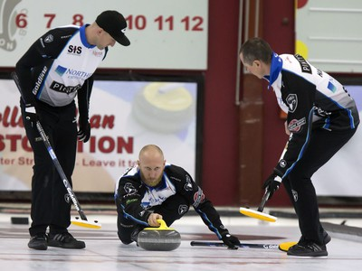 Skip Brad Jacobs (C) throws a rock with sweepers Ryan Harnden and E.J. Harnden in action during the championship final in the World Curling Tour's College Clean Restoration Curling Classic at the Nutana Curling Club, September 26, 2016.