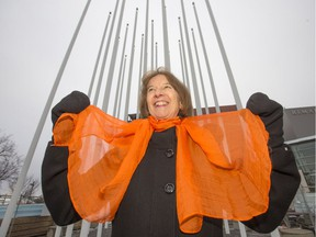 Jenny Neal, regional director of the Grandmothers Advocacy Network for Saskatchewan and Manitoba, displays her orange scarf at the sculpture Prairie Wind at River Landing, Thursday, November 24, 2016, to promote 16 days of orange to raise awareness about violence against women.
