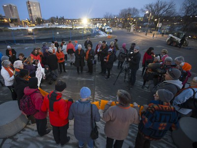 Participants in an orange rally organized by the Grandmothers Advocacy Network at the Prairie Wind Structure at River Landing, November 25, 2016. The statue itself and rally participants were dressed in orange as part of an international campaign to raise awareness and call for an end to violence against women and girls.