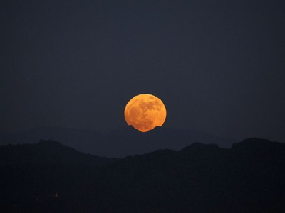 The moon rises behind the mountain range seen from Naypyitaw, Myanmar, November 14, 2016. The brightest moon in almost 69 years lights up the sky in a treat for star watchers around the globe. The phenomenon is known as the supermoon.