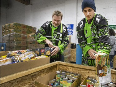 Saskatchewan Rush president Lee Genier (L) and defender Nik Bilic wear their ugly Christmas sweater jerseys while helping out at the Saskatoon Food Bank December 15, 2016.
