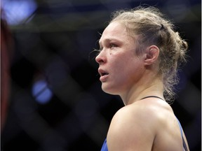 Ronda Rousey stands in the cage after Amanda Nunes forced a stoppage in the first round of their women's bantamweight championship mixed martial arts bout at UFC 207, Friday, Dec. 30, 2016, in Las Vegas.