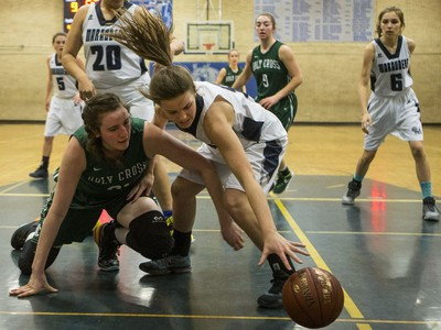 Holy Cross Crusaders' Kyla Shand (L) battles for a loose ball with Walter Murray Marauders Kami Hills in high school girl's basketball action at Walter Murray Collegiate in Saskatoon, January 17, 2017.