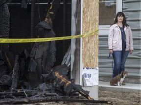 Suzanna D'Aprile, who was alerted to blaze at the home adjacent to hers by a passerby in middle of night, stands for a photograph with her dog Marty outside her home in Saskatoon, SK on Friday, April 7, 2017.