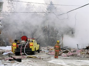 A firefighter looks over the wreckage of a Regina Beach home that exploded in December 2014 after shifting ground caused a natural gas leak.
