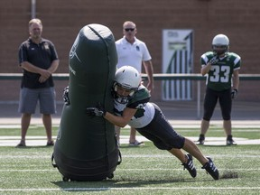 BESTPHOTO  SASKATOON,SK--AUGUST 18/2017-0819 Sports Football Robot-  Saskatoon Valkyries #22 Samantha Matheson tackles a robotic tackling dummy during a media event at SMF Field in Saskatoon, SK on Wednesday, August 18, 2017. David Dube has purchased a robotic tackling dummy that runs 20 miles an hour and is designed to train football players while reducing concussions.(Saskatoon StarPhoenix/Liam Richards) Liam Richards, Saskatoon StarPhoenix