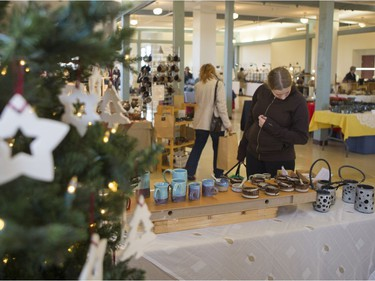 Lauren Konok looks at different pottery pieces for sale during the Saskatoon Potters Guild annual Christmas sale at the Albert Community Centre in Saskatoon on Saturday, November 25, 2017.