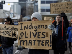 People gather with signs during a rally in response to Gerald Stanley's acquittal in the shooting death of Colten Boushie in Edmonton, Alta., on Saturday, February 10, 2018.