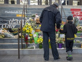 People gather at a memorial set up on the stairs that lead to Elgar Petersen Arena in Humboldt, Sask. on Saturday, April 7, 2018. Investigators are still trying to piece together what happened when a tractor-trailer collided with a hockey team bus at a Saskatchewan highway intersection in a horrific crash that killed 15 people, including players and the coach of the Humboldt Broncos.