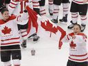 Team Canada players Gina Kingsbury, left, and Colleen Sostorics celebrate with the flag after winning the gold medal ice hockey game against Team USA at the Vancouver 2010 Olympics Feb. 25, 2010. The changes in women's hockey since Jacques Rogge threatened to kick it out of the Winter Olympics will be felt in Sochi, albeit subtly.