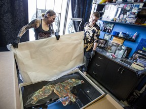 SASKATOON,SK--APRIL 12/2019-*0415 NEWS Tattoo -   Cheryl Wenzel, left, unpacks mounted pieces of tattooed skin at Electric Underground Tattoo with her son Cody Ross-Wenzel.  Wenzel, the wife of deceased tattoo artist Chris Wenzel, had ChrisÕs skin and his tattoos preserved through a company in the United States. ChrisÕ tattoos are set to be unveiled at the tattoo expo this weekend in Saskatoon on Friday, April 12, 2019. (Saskatoon StarPhoenix/Matt Smith)