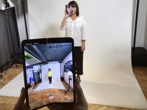 A model holds a Samsung Galaxy Fold smart phone to her face, during a media preview event in London on April 16, 2019.