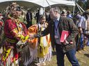 Dancer Kevin Haywahe, left, shakes hands with Alberta Premier Jason Kenney during a welcoming event outside the Sgt. Darby Morin Centre in Big River on July 9, 2019.