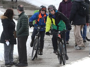Cyclists try to manoeuvre past people standing on the Meewasin Trail in Saskatoon on March 15, 2017.
