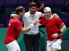 Vasek Pospisil and Denis Shapovalov celebrate with Canada team captain Frank Dancevic after defeating Australia in a quarterfinal doubles match at the Davis Cup in Madrid, Spain, on on Thursday, Nov. 21, 2019.