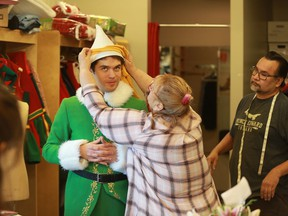 Bonnie Deakin helps fit the classic green Elf costume onto lead actor Felix LeBlanc during a costume fitting for Persephone Theatre's production of Elf: The Musical, which opens on Dec. 6, 2019.