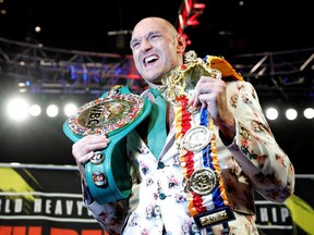 Tyson Fury poses with his belts during a press conference after the fight.