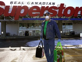 Edmonton resident Lloyd Kitchen leaves the Real Canadian Superstore in south Edmonton with groceries.