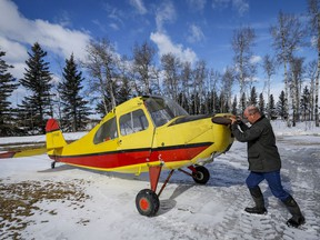 David Reid, a farmer and pilot pushes the plane that his father Richard purchased as a 17-year-old and which he is now restoring, out of a hangar at their farm near Cremona, Alta., Wednesday, March 4, 2020.THE CANADIAN PRESS/Jeff McIntosh